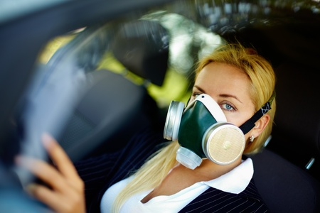 respirator: Photo of blond female breathing through respirator while driving in polluted area Stock Photo