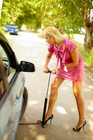 inflating: Photo of blond woman pumping wheels of her car on the road