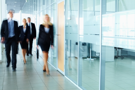 go inside: Several businesspeople walking in the corridor  Stock Photo