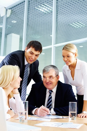 expertise: Business team of four people interacting in office at meeting Stock Photo