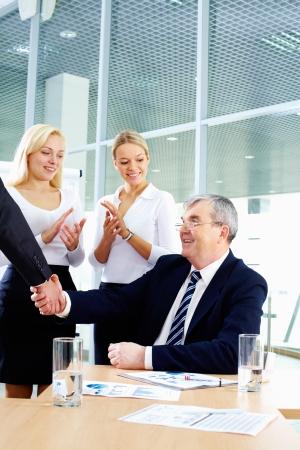 manos aplaudiendo: Jefe Senior estrecharme la mano con su pareja, mientras dos mujeres sobre fondo de Palmas de manos Foto de archivo