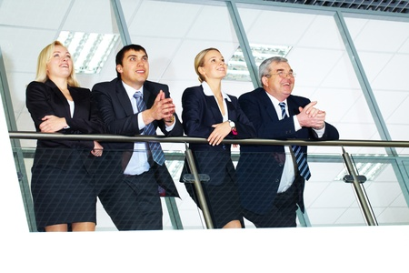 banisters: Group of businesspeople and their senior boss standing by banisters