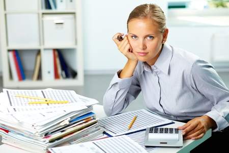 economist: Portrait of a young businesswoman at her workplace looking at camera Stock Photo