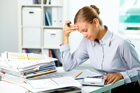 paperwork: Portrait of a young businesswoman working with papers in office Stock Photo