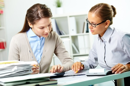 Portrait of young businesswomen working with papers in office photo