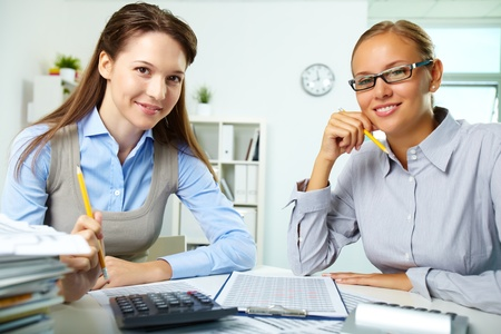 Portrait of happy young businesswomen looking at camera in office photo