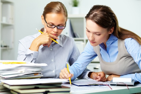 economist: Portrait of two businesswomen working with papers in office Stock Photo