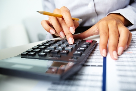 Photo of hands holding pencil and pressing calculator buttons over documents Stock Photo - 10289774