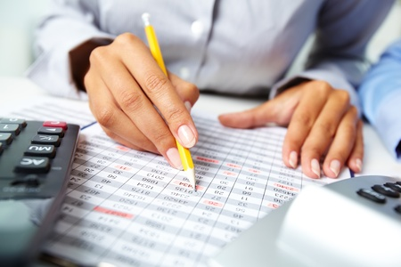 Photo of human hands holding pencil and marking numbers in documents  photo