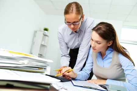 paperwork: Portrait of two businesswomen working with papers in office Stock Photo