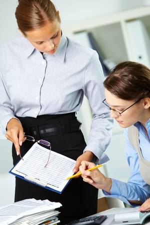 Portrait of two businesswomen discussing papers in office photo