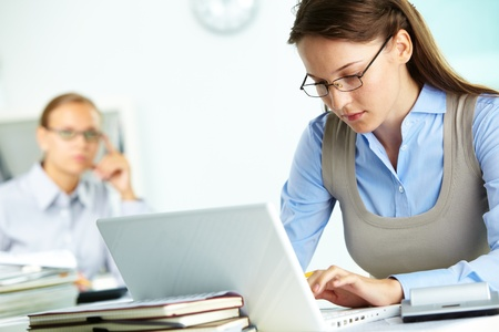 office environment: Portrait of pretty secretary typing in office Stock Photo