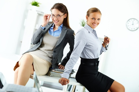 Portrait of happy young businesswomen posing in office photo