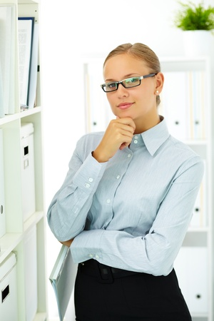 librarian: Portrait of elegant businesswoman looking at camera in office