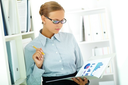 Portrait of elegant businesswoman working with papers in office photo