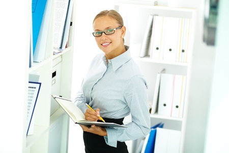 Portrait of elegant businesswoman looking at camera in office photo