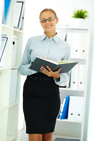 Portrait of elegant businesswoman with notepad looking at camera in office photo
