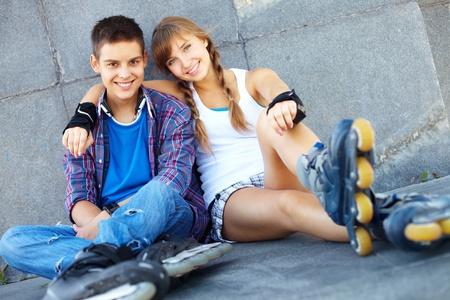 pareja de adolescentes: Pareja de adolescentes felices sobre patines mirando la cámara