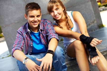 teen couple: Couple of happy teens looking at camera outside