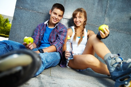 youthful: Couple of two happy teens with apples sitting outside
