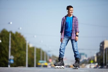 niño en patines: Imagen de adolescente feliz en patines en la ciudad