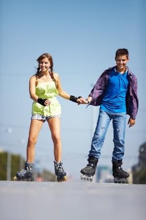pareja de adolescentes: Pareja de adolescentes felices rodando sobre patines en el camino