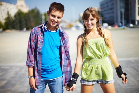 Couple of two happy roller skaters having good time outside photo