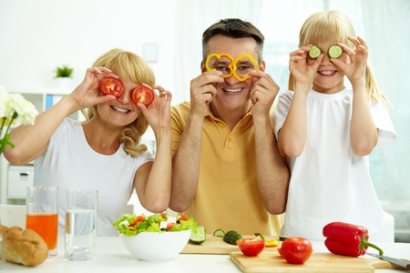mood: Portrait of happy parents and their daughter posing with vegetables in the kitchen  Stock Photo