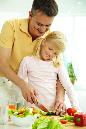 Portrait of happy father and daughter cooking vegetable salad in the kitchen  photo
