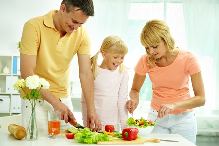 family kitchen: Portrait of happy parents and their daughter cooking salad in the kitchen  Stock Photo