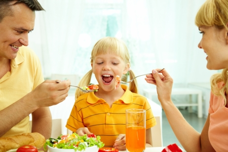 hungry kid: Portrait of happy parents feeding their daughter with salad in the kitchen  Stock Photo