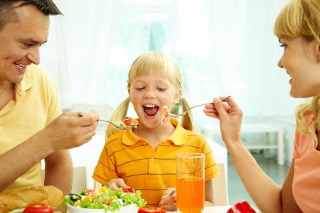mujer hijos: Retrato de felices padres alimentar a su hija con ensalada en la cocina