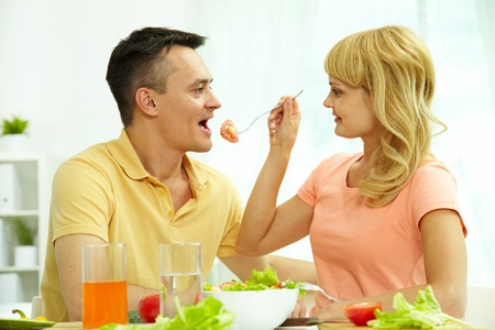 person appetizer: Image of woman giving her husband slice of tomato on fork