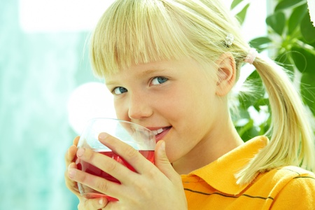 Portrait of happy girl drinking juice from glass and looking at camera  photo