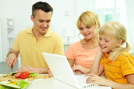 Portrait of man cutting vegetables for salad while his wife and daughter working with laptop the kitchen photo