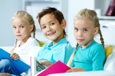 elementary students: Smart schoolboy looking at camera between twin girls