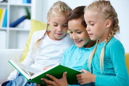 Smart schoolboy and twin girls reading book Stock Photo - 10309124