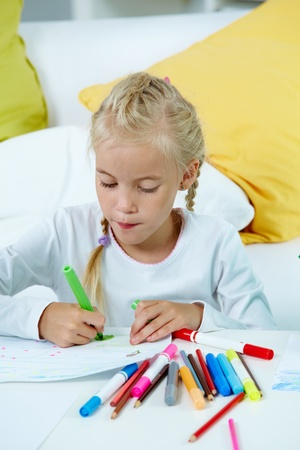 Portrait of lovely girl drawing with colorful pencils photo