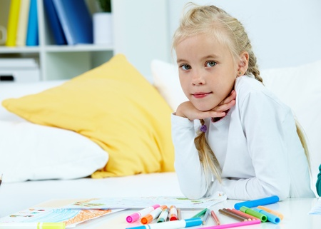 Portrait of lovely girl with her pictures and colorful pencils near by photo