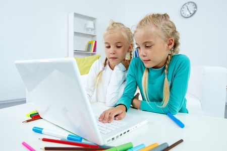 Portrait of twin girls studying in front of laptop photo