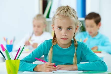 Portrait of lovely girl drawing with classmates on background photo