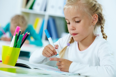 Portrait of lovely girl drawing with highlighters photo