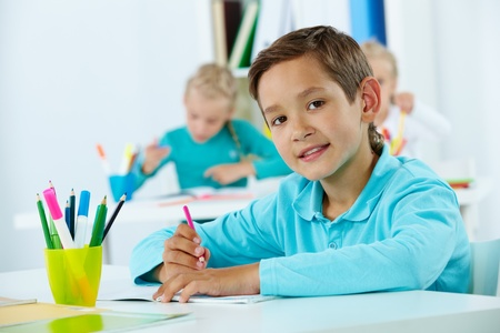 lad: Portrait of cute lad drawing with classmates on background