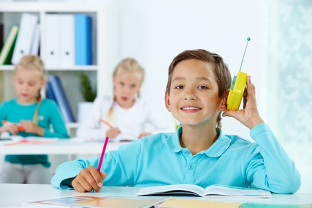 lad: Portrait of cute lad listening to radio while drawing with classmates at lesson
