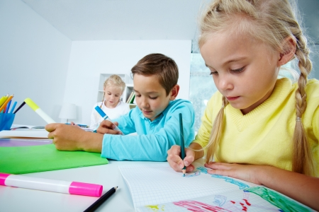 Portrait of lovely girl and her classmates drawing with highlighters at lesson photo