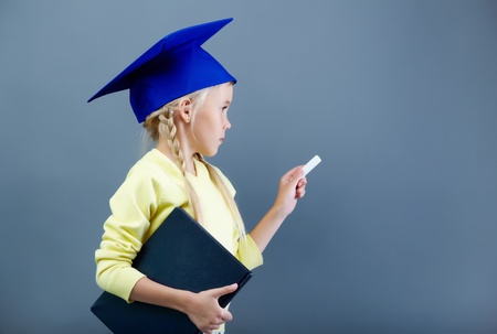Portrait of lovely girl in graduation hat writing with chalk photo