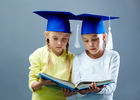 Portrait of lovely twin girls in hats with tassels reading book photo