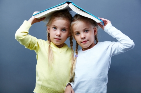 Portrait of lovely twin girls holding open book over heads Stock Photo
