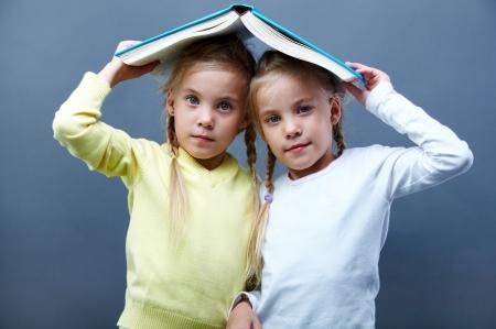 bambine gemelle: Ritratto di belle gemelle tenendo libro aperto sopra le teste Archivio Fotografico