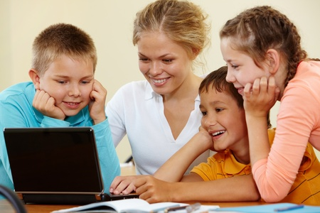 Smart schoolchildren and teacher working with laptop photo